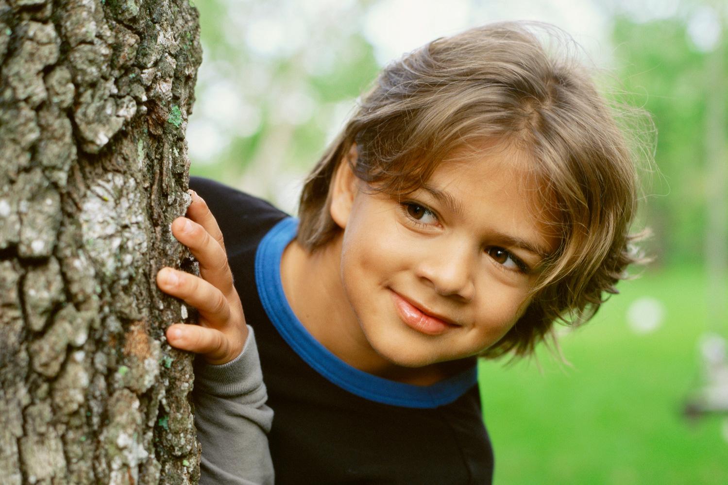 Ein Junge schaut hinter einem Baum hervor. Thema: Geheimtipps in Deutschland