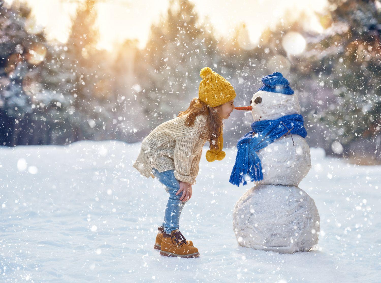 Ein Mädchen gibt einem Schneemann einen Nasenkuss in winterlicher Kulisse.