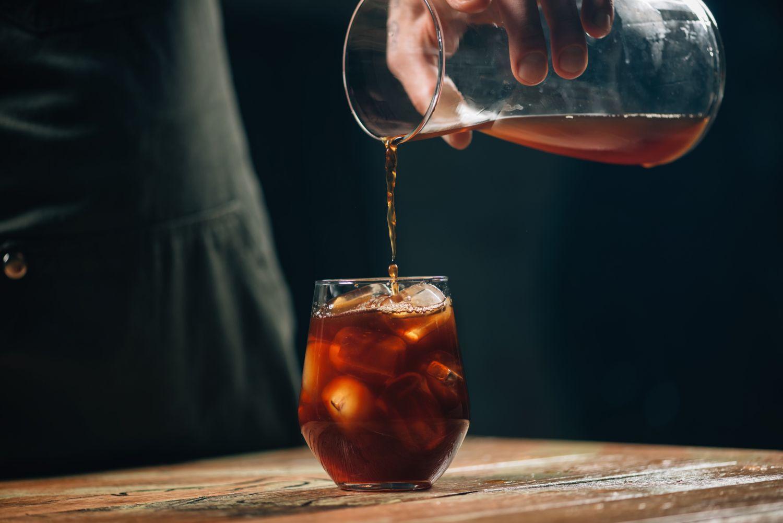 Jemand gießt Cold Crew in ein Glas. Thema: Kaffeevariationen