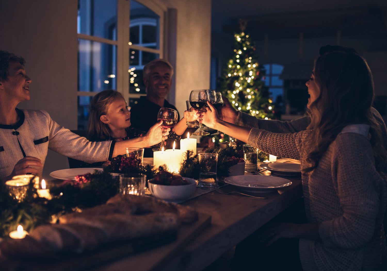 Eine Familie sitzt an der weihnachtlich dekorierten Tafel und stößt gemeinsam an.