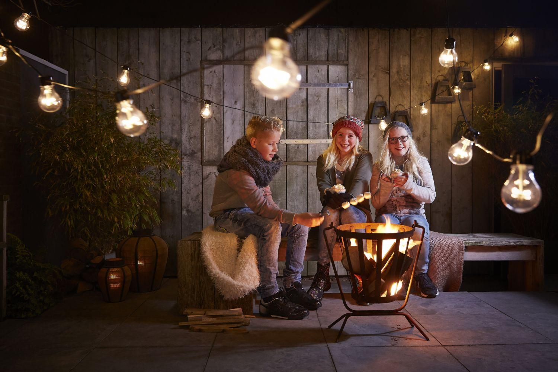 Kinder grillen Marshmallows über einem Feuer. Thema: Winter als Wohlfühlzeit