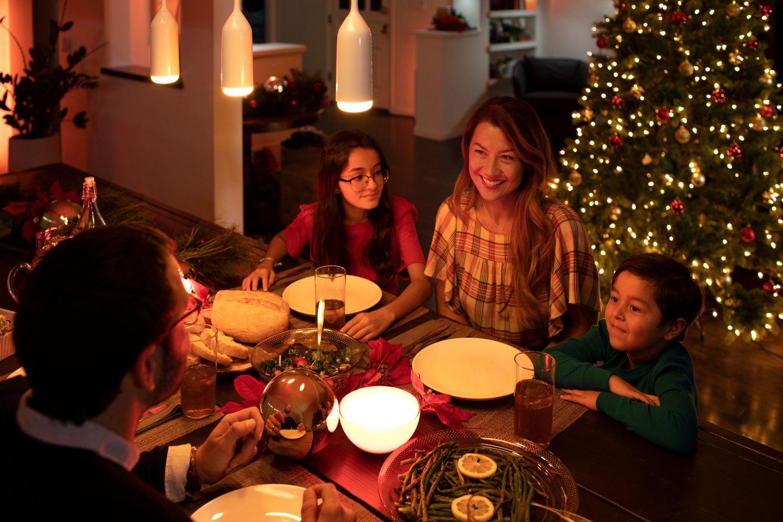 Familie sitzt an Weihnachten um den festlich gedeckten Tisch mit gemütlicher Beleuchtung
