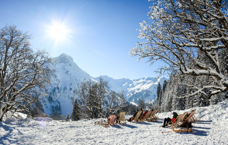Menschen sonnen sich auf Liegestühlen in einer Winterlandschaft.