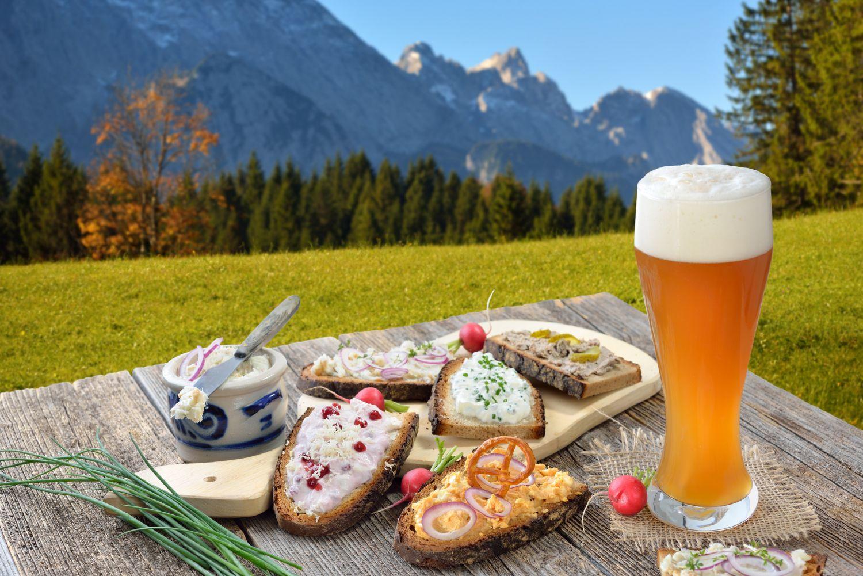 Herzhaftes Essen und ein Bier vor Bergpanorama in Süddeutschland.