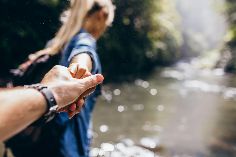 Eine Frau führt einen Mann an der Hand durch die Natur. Thema: Lebensqualität in Deutschland